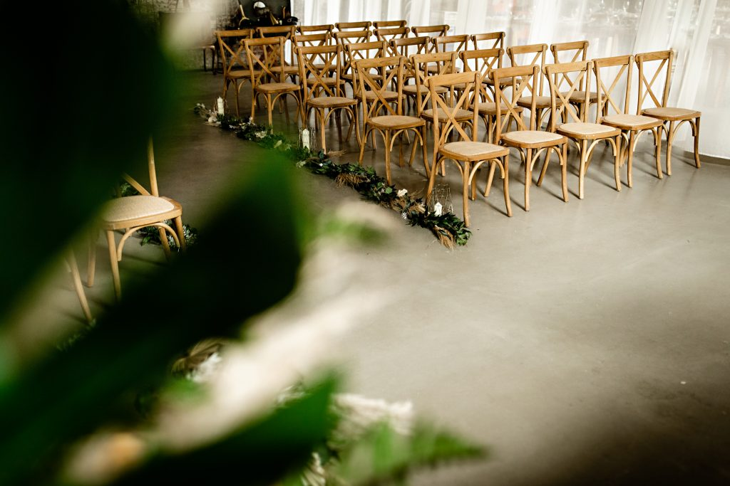 Wedding ceremony area with wooden crossback chairs