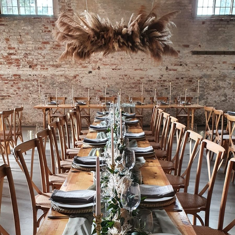 Wood trestle tables with pampas cloud