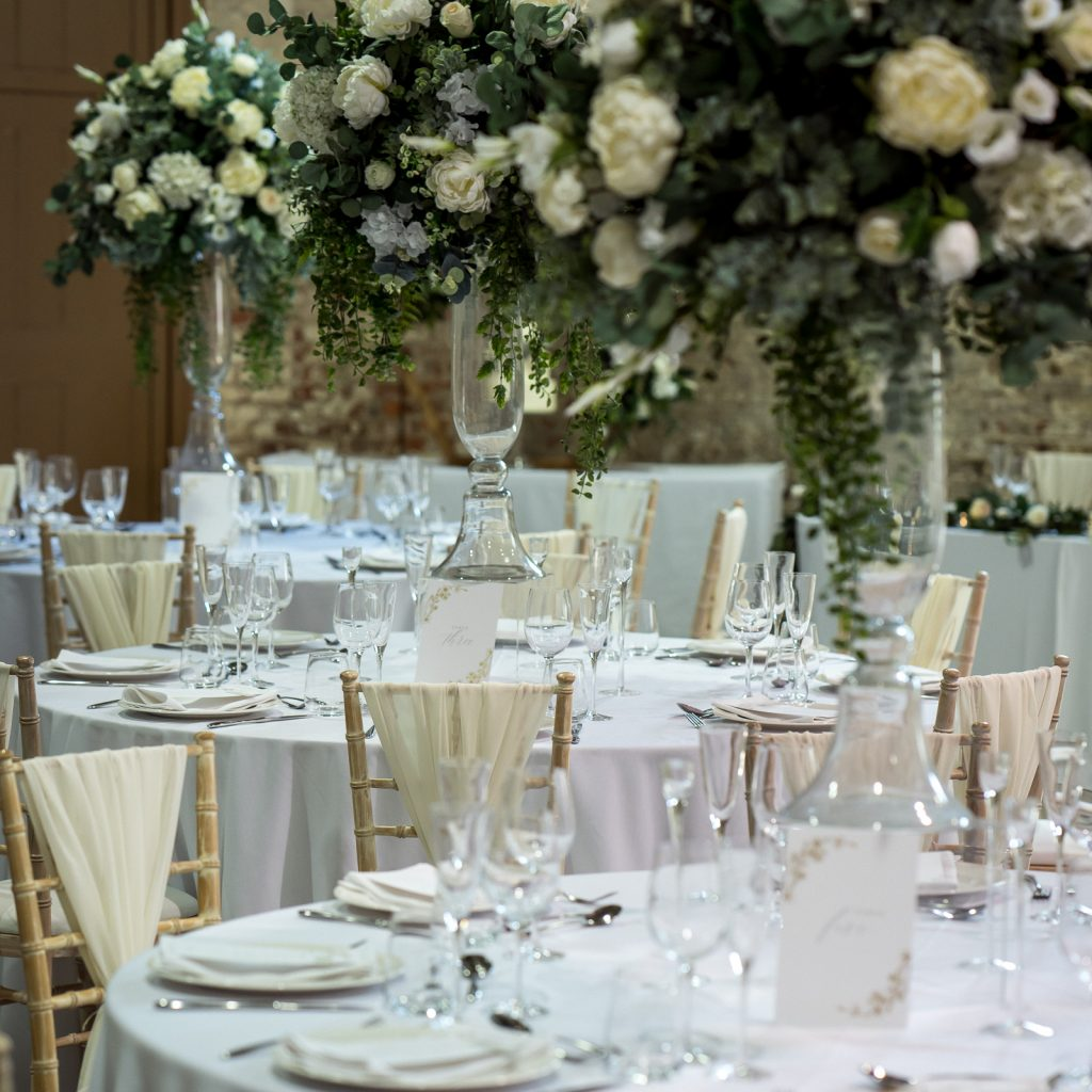 Round tables with luxurious white flower balls on tall glass risers