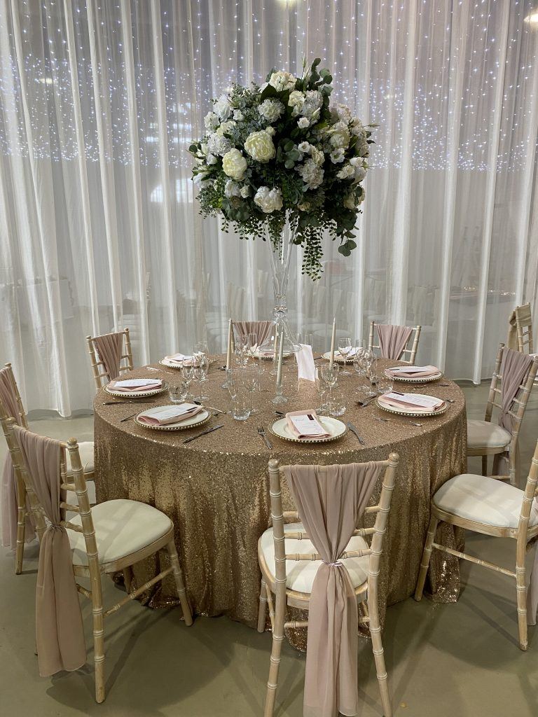 Wedding table set up with blush sequin linen and large white flowerball on a glass vase