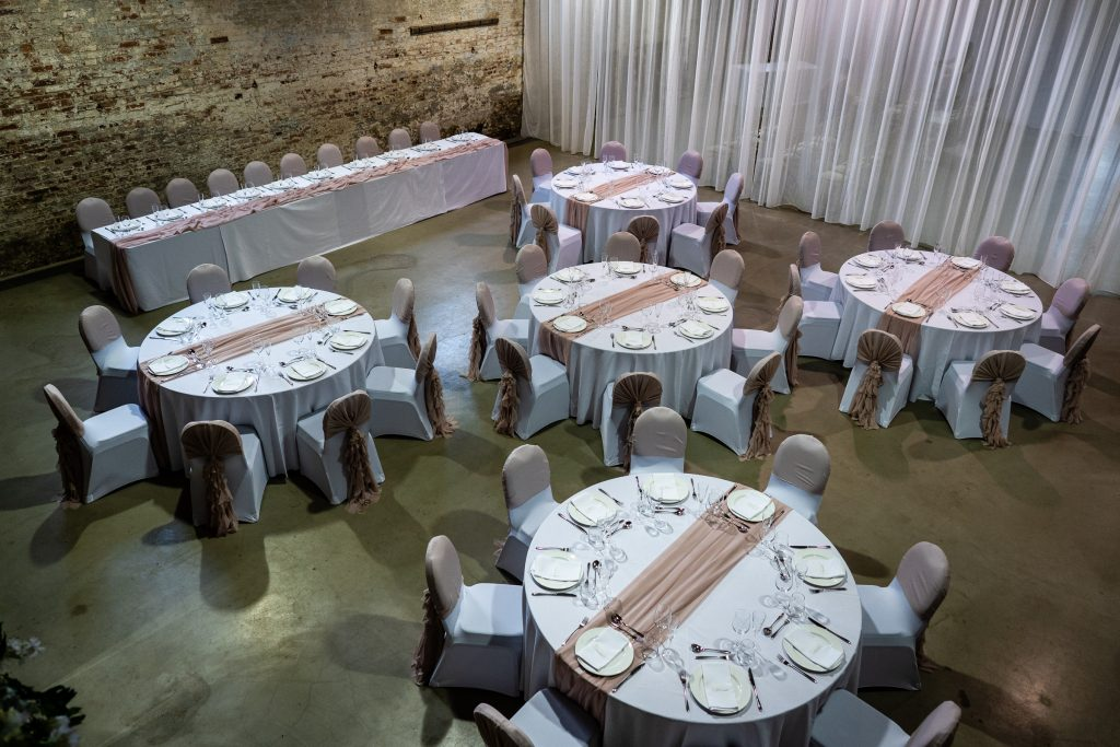 Wedding breakfast set up from above with five round tables and one top table