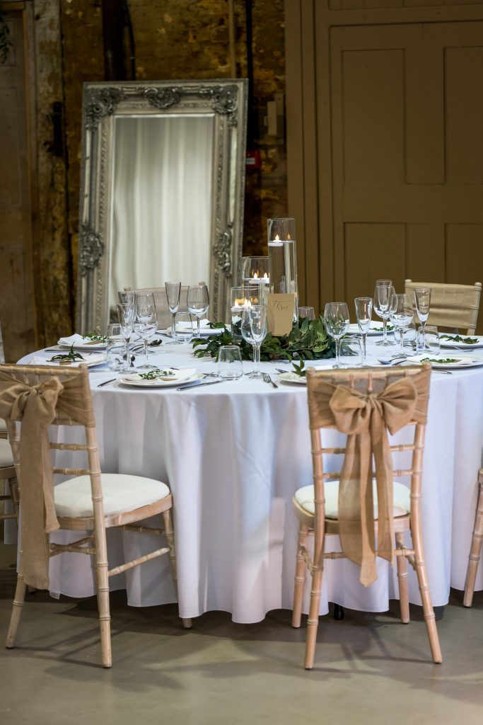 Wedding table set up with hessian chair bows and simple candle cluster centrepiece