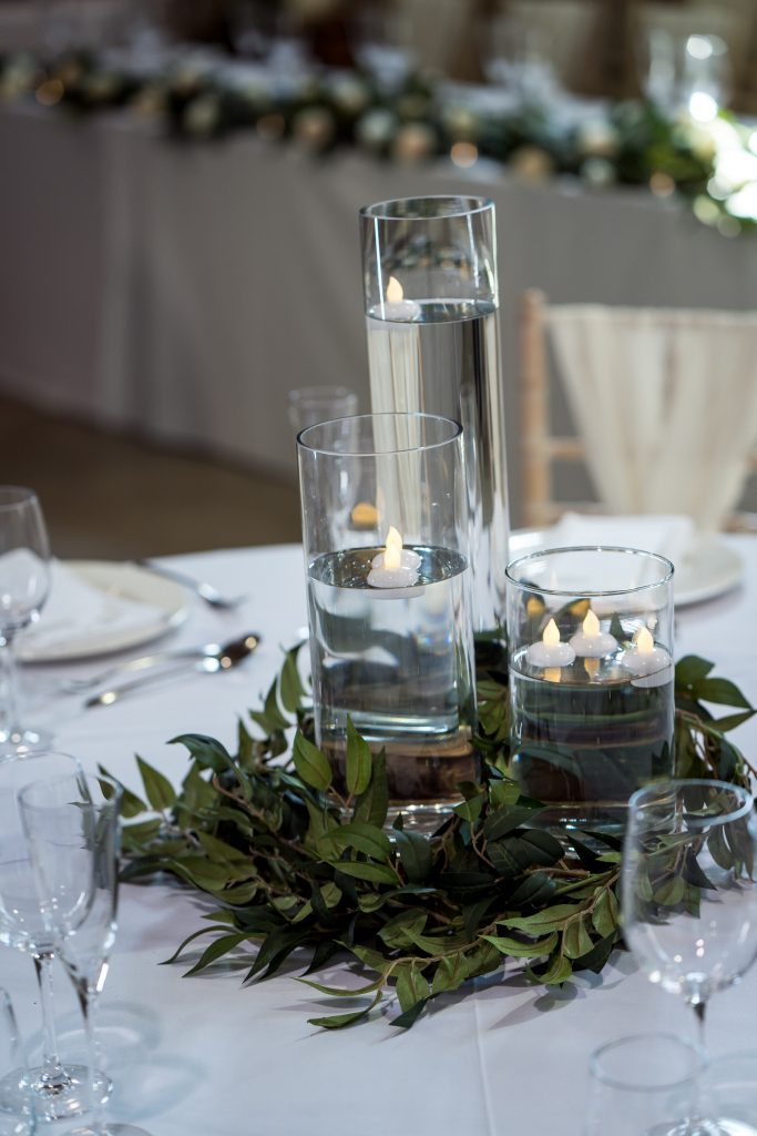 Tall cylinder vases with floating candles and greenery base