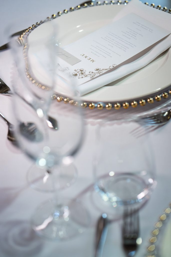 White table linen with glasswear and gold beaded charger plate