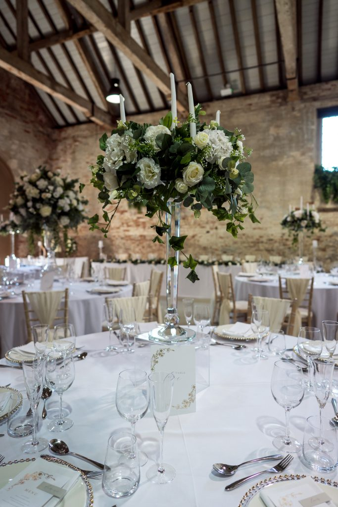 White table linen with large white flower balls on glass candelabras