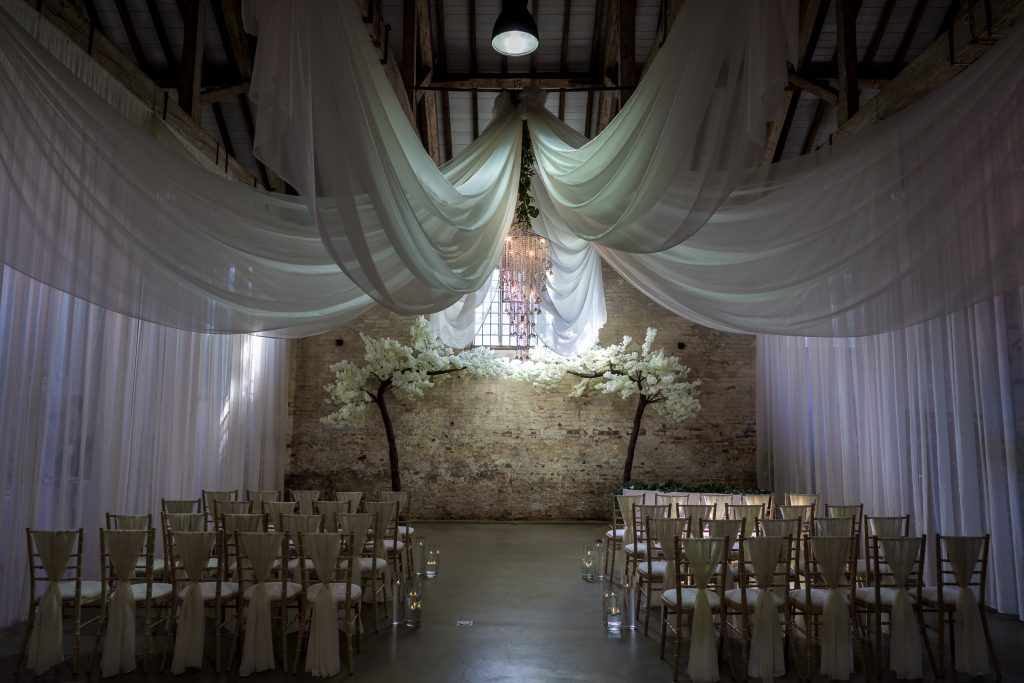 Chiffon drapes hanging from wooden ceiling beams with chandelier and blossom trees